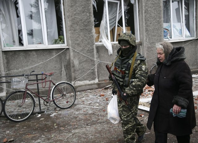 Soldier helps an elderly woman to carry a bag of supplies outside of the humanitarian aid distribution center in the town of Debaltseve, Ukraine, Friday, February 6, 2015. (Photo by Petr David Josek/AP Photo)