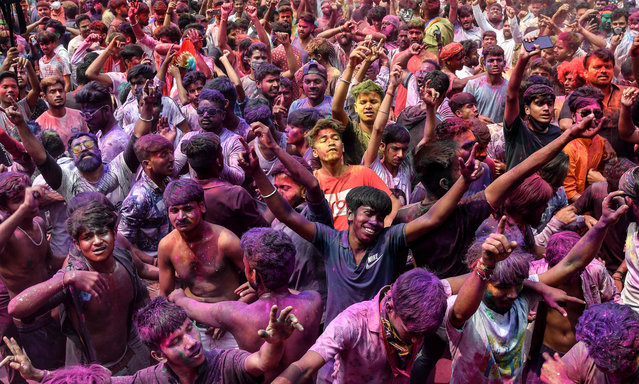 Revellers smeared in colour powder celebrate the Holi, the spring festival of colours, on a street in Guwahati on March 29, 2021. (Photo by Biju Boro/AFP Photo)