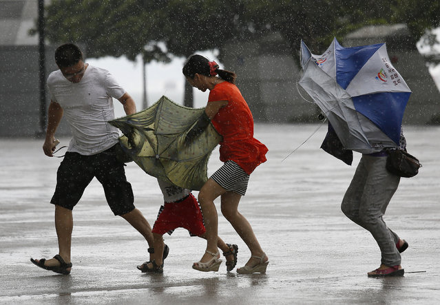 A family battle against the strong wind near the waterfront in Hong Kong Wednesday, August 14, 2013. Typhoon Utor lashed Hong Kong with wind and rain, closing down the bustling Asian financial center Wednesday before sweeping toward mainland China. (Photo by Vincent Yu/AP Photo)