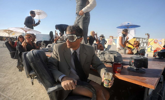 """A """"Mobile Board Room"""" moves along the playa at the Burning Man festival in Gerlach, Nev. on Thursday, Aug. 29, 2013. Once a year, tens of thousands of participants gather in Nevada's Black Rock Desert for the counterculture event. (Photo by Andy Barron/AP Photo/Reno Gazette-Journal)"""