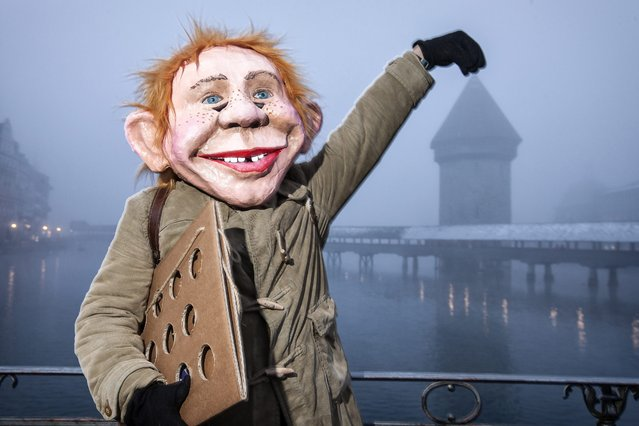 A masked reveller parades through the streets on the first day of the carnival season in Lucerne, Switzerland, 12 February 2015. In the background the well known Kappellbruecke bridge. (Photo by Alexandra Wey/EPA)