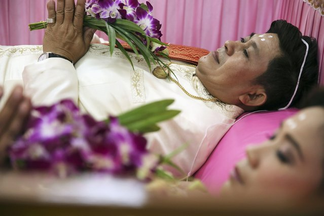 A groom and a bride hold flowers inside a pink coffin during their wedding ceremony at Wat Takien temple in Nonthaburi province, on the outskirts of Bangkok February 14, 2015. (Photo by Damir Sagolj/Reuters)