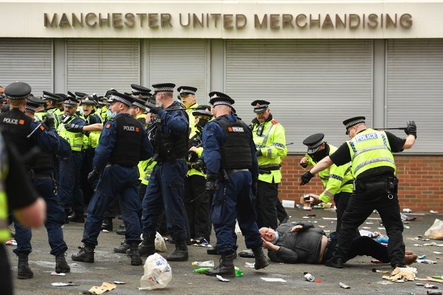 A protester falls behind the police line as police move people away from the stadium after a supporter's protest against Manchester United's owners, outside English Premier League club Manchester United's Old Trafford stadium in Manchester, north west England on May 2, 2021, ahead of their English Premier League fixture against Liverpool. Manchester United were one of six Premier League teams to sign up to the breakaway European Super League tournament. But just 48 hours later the Super League collapsed as United and the rest of the English clubs pulled out. (Photo by Oli Scarff/AFP Photo)