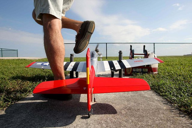 Dusty Rhoads of Jupiter steps over his P51 remote control plane. (Photo by Bill Ingram/The Palm Beach Post)