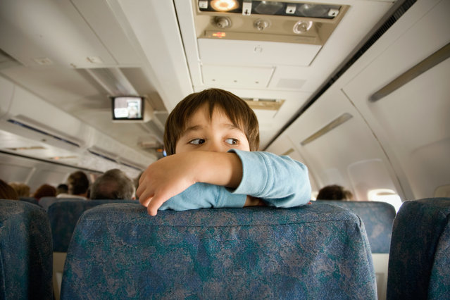 3-4 year old boy climbing and looking over the airplane seat. (Photo by Keiji Iwai/Getty Images)