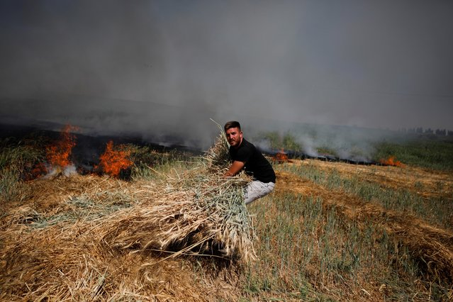 A man moves a bundle of wheat as a fire burns on a field after a rocket launched from the Gaza Strip landed near homes in Moshav Zohar, Israel on May 13, 2021. (Photo by Amir Cohen/Reuters)