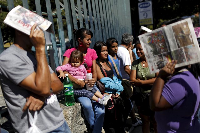 People line up to try to buy staple food and household items, outside a supermarket in Caracas January 16, 2016. (Photo by Carlos Garcia Rawlins/Reuters)