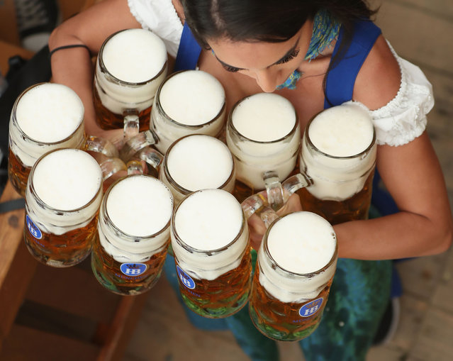 A waitress carries beer steins in a beer tent on the opening day of the 2018 Oktoberfest beer festival on September 22, 2018 in Munich, Germany. The Oktoberfest lasts until October 7 and is the world's largest beer festival. The beer festival typically draws over six million visitors. (Photo by Alexandra Beier/Getty Images)