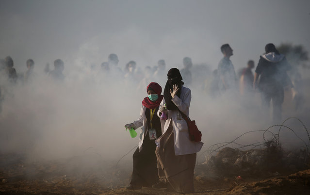 Palestinian medics walk out during a protest calling for lifting the Israeli blockade on Gaza and demanding the right to return to their homeland, at the Israel-Gaza border fence in the southern Gaza Strip October 12, 2018. (Photo by Ibraheem Abu Mustafa/Reuters)