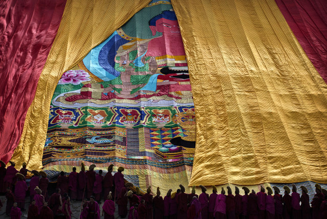 Tibetan Buddhist Monks of the Gelug, or Yellow Hat order, unveil a large thangka showing Buddha during Monlam or the Great Prayer rituals on March 3, 2015 at the Labrang Monastery, Xiahe County, Amdo, Tibetan Autonomous Prefecture, Gansu Province, China. (Photo by Kevin Frayer/Getty Images)