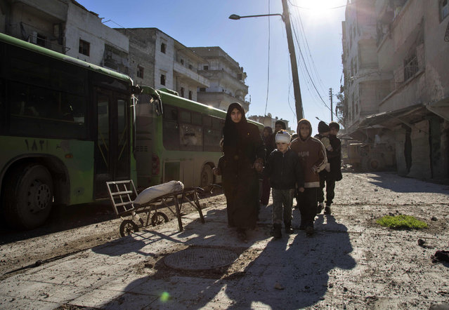 Syrians gather during an evacuation operation of rebel fighters and their families  from rebel-held neighbourhoods on December 15, 2016 in the embattled city of Aleppo. A convoy of ambulances and buses left rebel territory in Aleppo in the first evacuations under a deal for opposition fighters to leave the city after years of fighting. The rebel withdrawal will pave the way for President Bashar al-Assad's forces to reclaim complete control of Syria's second city, handing the regime its biggest victory in more than five years of civil war. (Photo by Karam Al-Masri/AFP Photo)