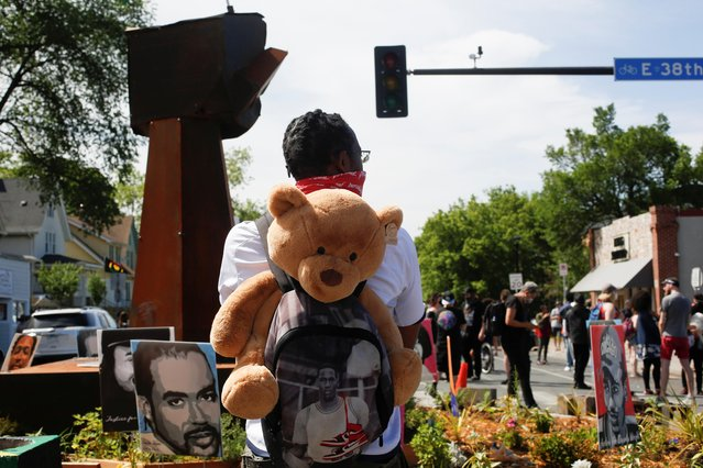 Michael Wilson looks over the fist sculpture and the gathering crowd after city employees began to reopen George Floyd Square, the area where George Floyd was killed in Minneapolis police custody the year before, in Minneapolis, Minnesota, U.S., June 3, 2021. (Photo by Nicole Neri/Reuters)