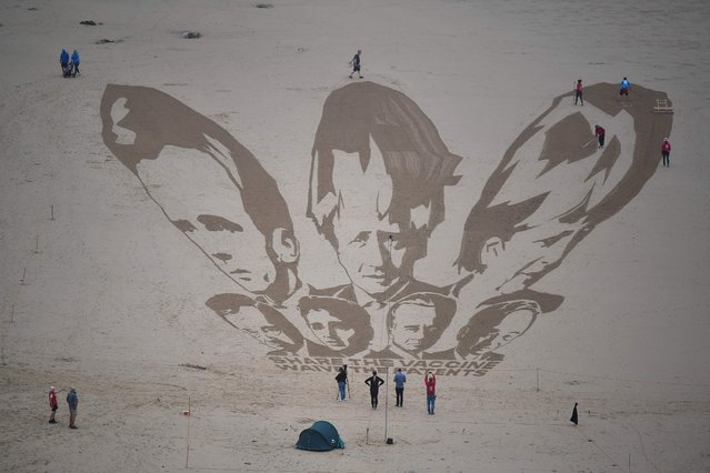 Activists put the finishing touches to a sand drawing of the G7 leaders and calling on them to 'share the vaccine and waive the patents' on Watergate Bay beach near Newquay, Cornwall on June 10, 2021, ahead of the three-day G7 summit being held from 11-13 June. G7 leaders from Canada, France, Germany, Italy, Japan, the UK and the United States meet this weekend for the first time in nearly two years, for the three-day talks in Carbis Bay, Cornwall. (Photo by Ben Stansall/AFP Photo)