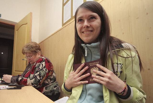 A woman reacts while holding a Russian passport after she received it at an office of the Russian federal migration service in Simferopol April 8, 2014. (Photo by Reuters/Stringer)