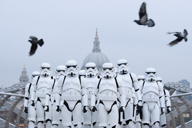 """People dressed as Stormtroopers from the Star Wars franchise of films pose on the Millennium Bridge to promote the latest release in the series, """"Rogue One"""", on December 15, 2016 in London, England. """"Rogue One: A Star Wars Story"""" is the first of three standalone spin-off films and is due for released in the UK today. (Photo by Leon Neal/Getty Images)"""