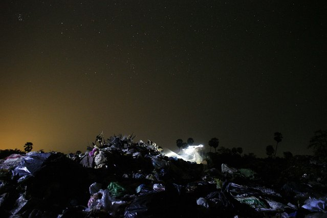 A headlamp leaves a light trace on a long exposure picture as a person looks for usable items at a landfill dumpsite outside Siem Reap March 18, 2015. (Photo by Athit Perawongmetha/Reuters)