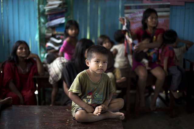 "In this March 16, 2015 photo, an Ashaninka boy sits quietly during a weekly community meeting inside a one-room school house in Saweto, Peru. Like other Ashaninka hamlets, Saweto holds weekly meetings to discuss local issues, where all adults have the right to address the gathering. A former regional ombudsman advising the community, said only a few bureaucratic hurdles remain to obtain the title to their ancestral tract bordering Brazil, but it's ""no guarantee against illegal logging"". (Photo by Martin Mejia/AP Photo)"