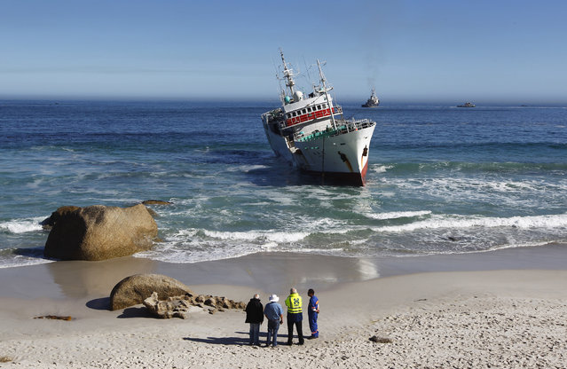 Salvage officials look on as a tugboat attempts to refloat fishing vessel Eihatsu Maru which ran aground at Clifton, one of Cape Town's most popular tourist beaches, May 15, 2012. (Photo by Mike Hutchings/Reuters)