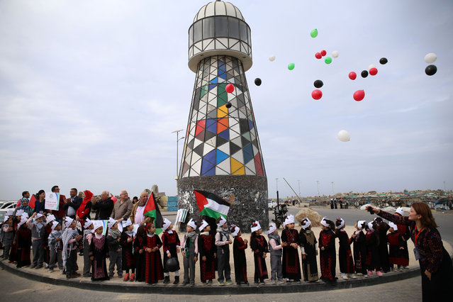 Palestinian children fly ballons during a gathering at the seaport in Gaza City to mark International Day of Solidarity with the Palestinian People on November 29, 2016. United Nations celebrates the International Day of Solidarity with the Palestinian People on November 29 or so each year. (Photo by Mohammed Abed/AFP Photo)