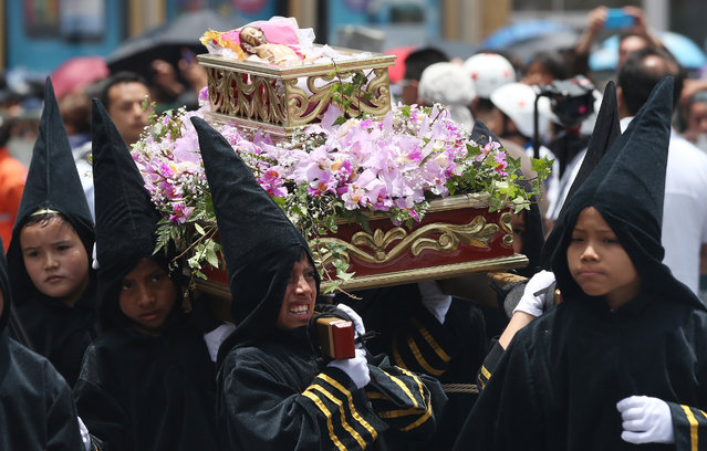 Young boys dressed as penitents carry the religious float representing the 14th station of the cross, when the body of Jesus is placed in a tomb, in the Children's Holy Thursday Procession, in Tunja, Colombia, Thursday, April 2, 2015. (Photo by Fernando Vergara/AP Photo)