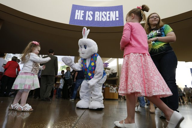 Rylee Choat, left, of Altoona, Iowa, waves to the Easter Bunny as Abby McCullough, right, hands out stickers to arriving children, Sunday, April 5, 2015, at the Easter service at Lutheran Church of Hope in West Des Moines, Iowa. (Photo by Michael Zamora/AP Photo/The Des Moines Register)
