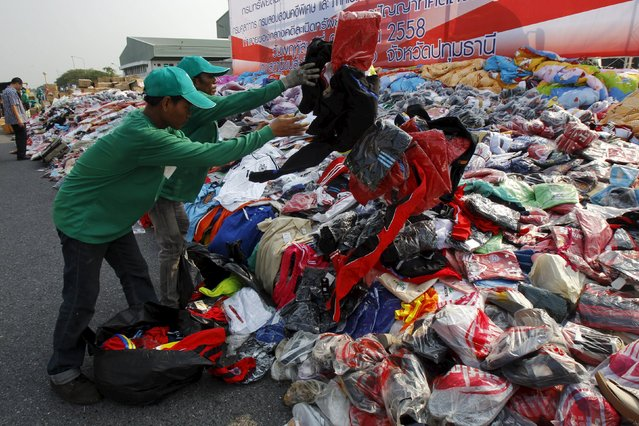 Thai officials arrange clothes before destroying them at Khlongluang Transportation Station in Pathumtani province, on the outskirts of Bangkok April 9, 2015. (Photo by Chaiwat Subprasom/Reuters)