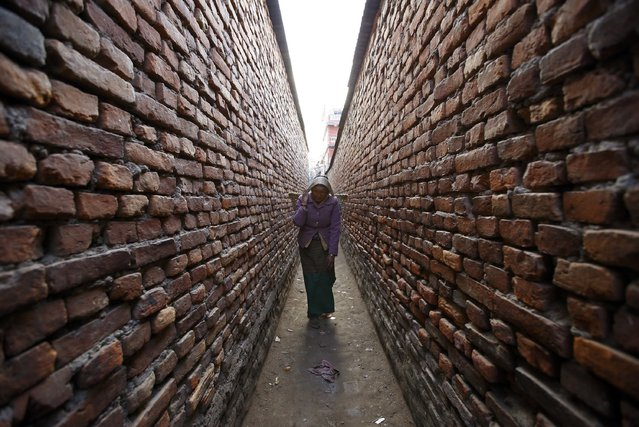 A woman carrying a basket walks down a narrow alley as she returns from the vegetable market in Kathmandu February 9, 2015. (Photo by Navesh Chitrakar/Reuters)
