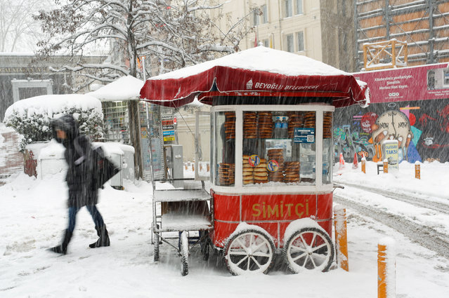 A street vendor sells simit, the traditional Turkish sesamed bread, at the main shopping and pedestrian street of Istiklal during a snowfall in central Istanbul, Turkey January 9, 2017. (Photo by Murad Sezer/Reuters)