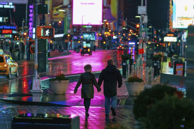 A couple walks through Times Square in the early morning Sunday, January 20, 2019, in New York. The National Weather Service said on Saturday that a dramatic drop in temperatures could turn the weekend's rainfall into ice before Monday. (Photo by Kevin Hagen/AP Photo)