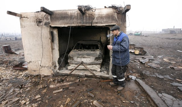 Local resident Gennady Simonov smokes near his burnt garage, with a BMW car inside, in the settlement of Shyra, damaged by recent wildfires, in Khakassia region, April 13, 2015. (Photo by Ilya Naymushin/Reuters)
