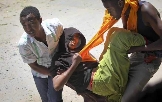 A person is assisted after being wounded when a car bomb detonated at the gates of a government office complex in the capital Mogadishu, Somalia Tuesday, April 14, 2015. (Photo by Farah Abdi Warsameh/AP Photo)