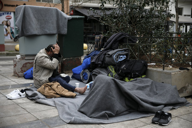 A stranded Afghan migrant (L) reacts as another sleeps on Victoria square in Athens, Greece, February 24, 2016. (Photo by Alkis Konstantinidis/Reuters)