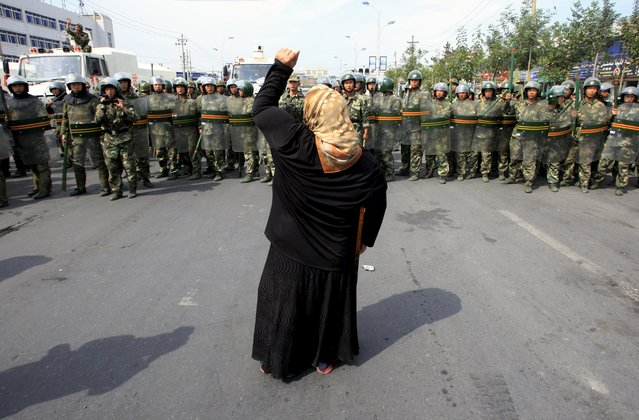 A local woman on a crutch shouts at Chinese paramilitary police wearing riot gear as a crowd of angry locals confront security forces on a street in the city of Urumqi in China's Xinjiang Autonomous Region, in this July 7, 2009 file photo. (Photo by David Gray/Reuters)