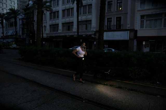 A woman walks her dog in downtown New Orleans at dawn during a blackout in the city after Hurricane Ida made landfall in Louisiana, U.S., August 31, 2021. (Photo by Marco Bello/Reuters)