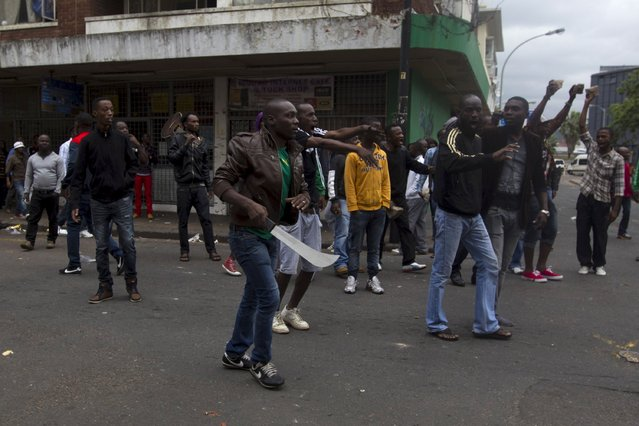A group of foreign nationals threaten to defend themselves as police get between them and South Africans after a peace march in Durban, April 16, 2015. At least four people have been killed in a wave of anti-immigrant violence that started two weeks ago in Durban, a key port on South Africa's Indian Ocean coast. (Photo by Rogan Ward/Reuters)