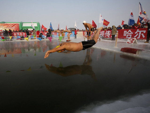A swimmer dives into a pool carved into the thick ice covering the Songhua River during the Harbin Ice Swimming Competition in the northern city of Harbin, Heilongjiang province January 5, 2014. (Photo by Kim Kyung-Hoon/Reuters)