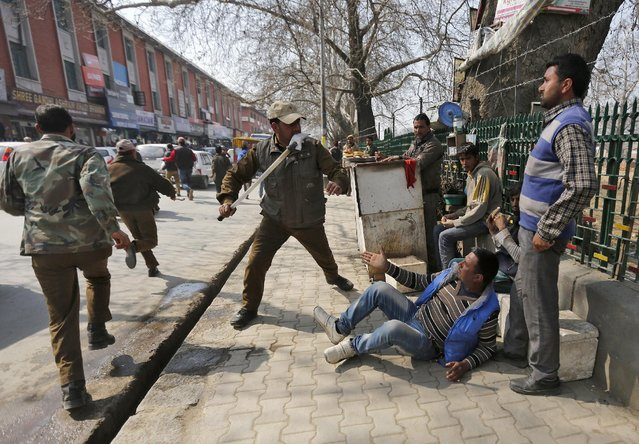 An Indian policeman wields his baton against a teacher during a protest in Srinagar, India February 29, 2016. Dozens of government teachers on Monday held a protest to demand regularisation of contractual teachers and hike in salaries, protesters said. (Photo by Danish Ismail/Reuters)