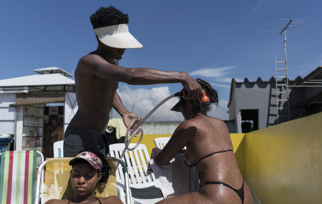 In this January 15, 2017 photo, an employee sprays a customer wearing a bikini made out of black electrical tape, in order to attain crisp tan lines, at the rooftop Erika Bronze salon in the suburb of Realengo in Rio de Janeiro, Brazil. Despite being sprinkled with water, some tanners feel dizzy or even faint after a rooftop session. (Photo by Renata Brito/AP Photo)