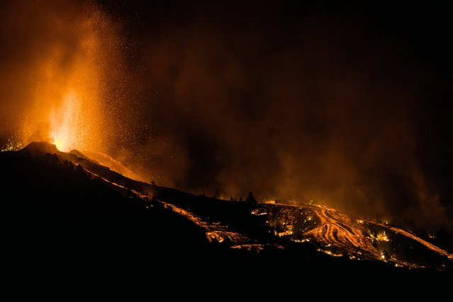 Lava flows from an eruption of a volcano at the island of La Palma in the Canaries, Spain, Sunday, September 19, 2021. (Photo by Jonathan Rodriguez/AP Photo)
