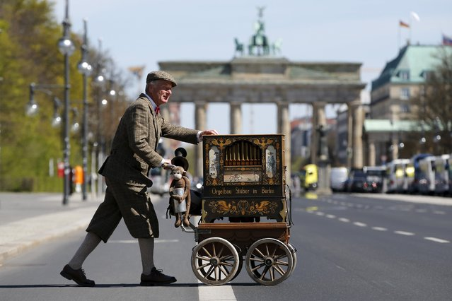 An organ grinder crosses the street in front of the Brandenburg Gate in Berlin April 20, 2015. (Photo by Fabrizio Bensch/Reuters)