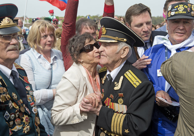 Russian veteran Nikolai Mihalovic Beljajev, 92, center right, dances with Hannelore Danders, center left, during the 70th anniversary celebrations of the so-called Elbe Day in Torgau, eastern Germany, Saturday, April 25, 2015. (Photo by Jens Meyer/AP Photo)