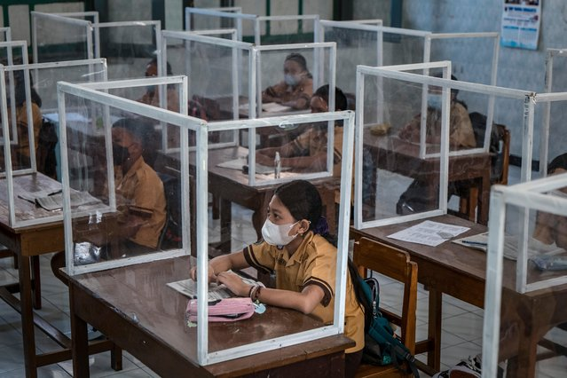 Indonesian students wear face masks and sit at desks with plastic screens used for social distancing at the Warga elementary school on September 03, 2021 in Solo City, Central Java, Indonesia. Indonesia is easing restrictions gradually as cases fall in the island of Java and Bali. With the easing, some schools are allowed to hold limited face-to-face learning, with classes held at 50 percent of the usual capacity. (Photo by Ulet Ifansasti/Getty Images)