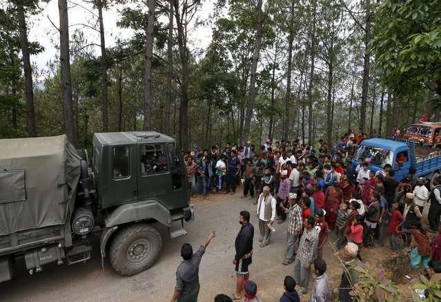 People force an army truck carrying relief supplies off the road, saying they have not received any government food aid five days after Saturday's earthquake, near Chautara, Nepal, April 29, 2015. (Photo by Olivia Harris/Reuters)