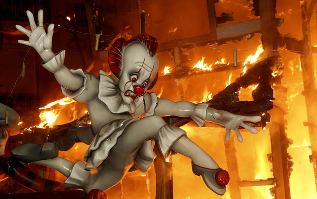 A falla ninot burns during the traditional Fallas festival in Valencia, Wednesday March 20, 2019. Fallas are gigantic structures made of cardboard portraying current events and personalities in which individual figures or Ninots are placed. (Photo by Alberto Saiz/AP Photo)