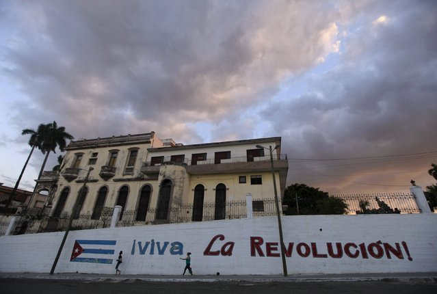 """People walk beside graffiti with a Cuban flag, during sunset in Havana March 8, 2016. The words read as """"Long live the Revolution"""". (Photo by Enrique de la Osa/Reuters)"""
