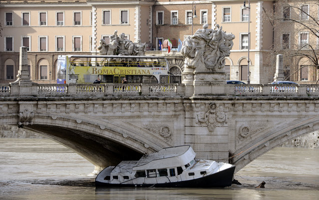 A boat crashed against the Vittorio Emanuele II's bridge over Tiber river in Rome on February 3, 2014, as water levels rise following heavy rain in the region. Heavy rains and windstorms battered Italy on February 1, swelling rivers and flooding fields and roads, while alpine areas saw abundant snow. (Photo by Andreas Solaro/AFP Photo)