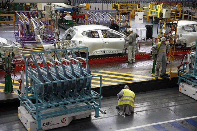 Employees work on the automobile assembly line of a Renault Clio IV at the Renault automobile factory in Flins, west of Paris, France, May 5, 2015. (Photo by Benoit Tessier/Reuters)