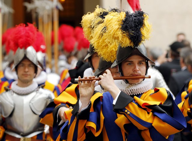 A new recruit of the Vatican's elite Swiss Guard plays a wind instrument as they march during the swearing-in ceremony at the Vatican May 6, 2015. (Photo by Giampiero Sposito/Reuters)