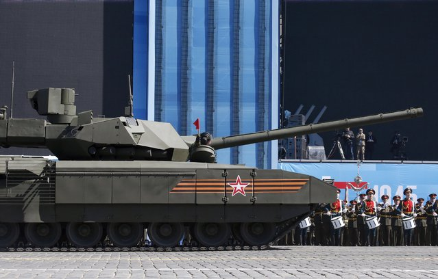 """A Russian serviceman holds a red flag onboard a T-14 Armata tank after it stopped during a rehearsal for the Victory Day parade in Red Square in central Moscow, Russia, May 7, 2015. A new high tech battle tank hailed by Russia as a """"masterpiece"""" appeared to break down on Red Square on Thursday during a rehearsal for the military parade at which it will make its long-awaited debut. (Photo by Grigory Dukor/Reuters)"""
