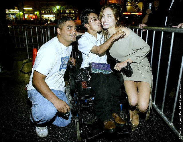Actress Angelina Jolie signs autographs for a man in a wheelchair